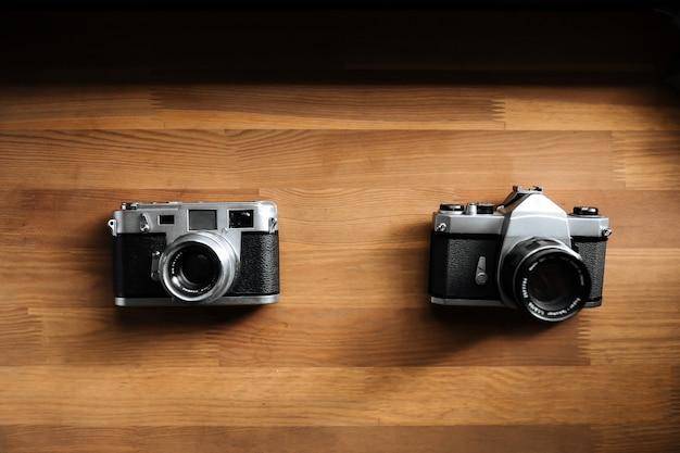 Deux appareils photo argentiques rétro se trouvent sur une table en bois