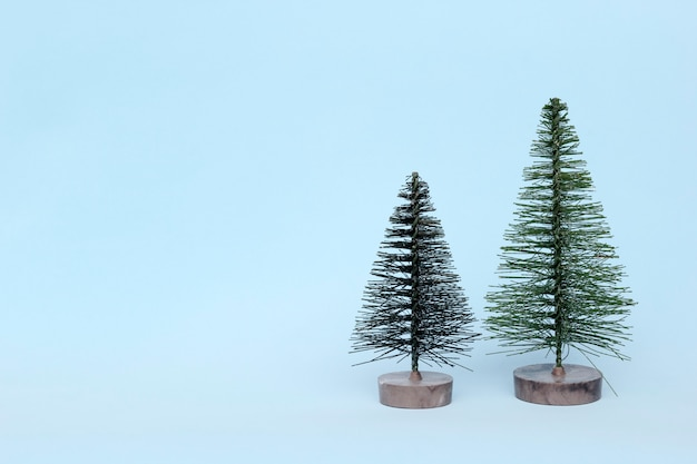 Deux arbres de noël sur fond clair dans un style minimal. décorations de noël, nouvel an et concept d'hiver.