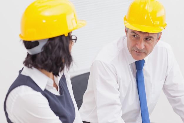 Deux architectes parlant avec un casque jaune