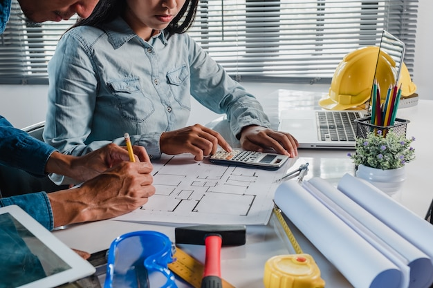 Deux architectes travaillant et discutant des données avec ordinateur portable et blueprint et calculatrice