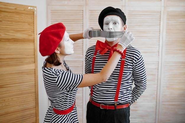 Deux artistes mime avec ruban adhésif, comédie parodique