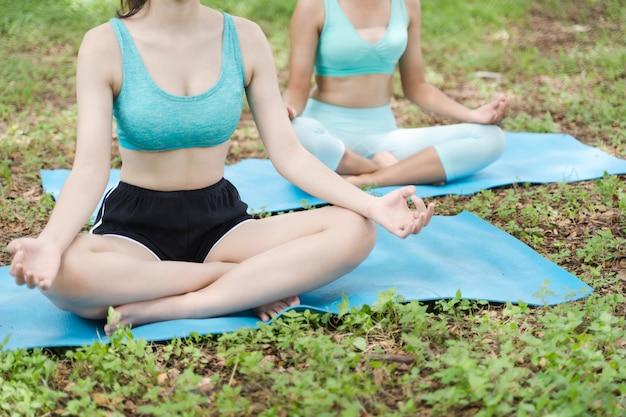 Deux asiatiques jeune athlète attrayante pratiquant le yoga dans la nature du parc en plein air sur l'herbe verte le matin, mode de vie de méditation et de détente saine