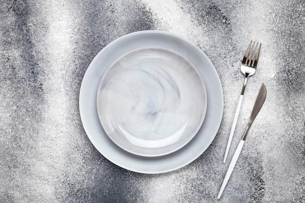 Deux assiettes en céramique vides et un couteau propre avec fourchette, vaisselle sur une table grise grunge, concept de service. conception à plat. le menu du restaurant. carte de voeux, mise en page, maquette avec espace de copie. vue aérienne.