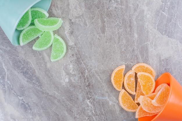 Deux assiettes colorées pleines de marmelades de sucre sur fond de marbre.