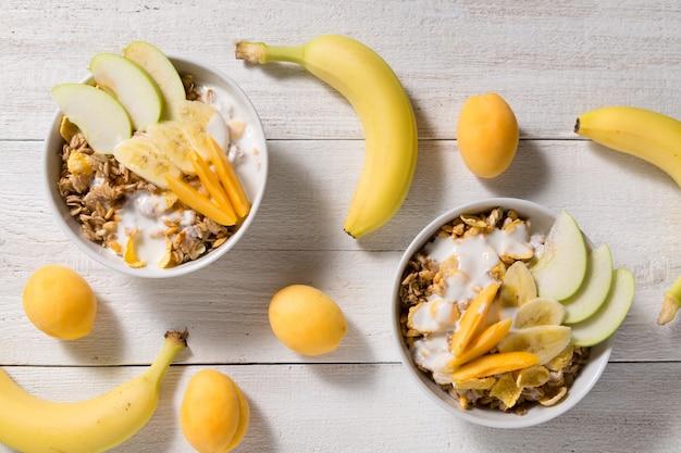 Deux assiettes avec flocons d'avoine et tasses de cornflakes et de riz soufflé sur un fond en bois blanc