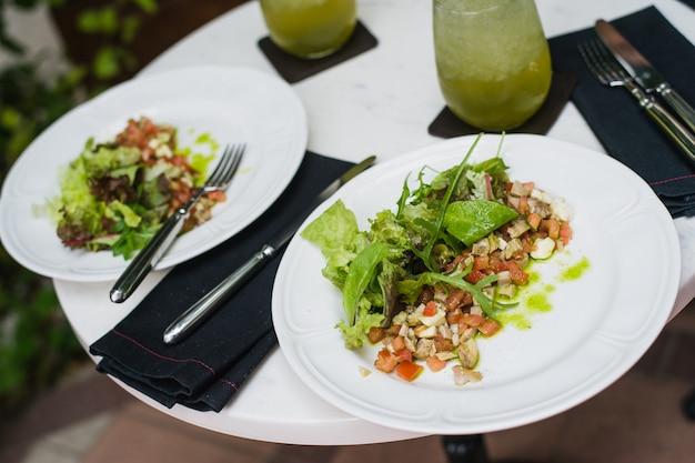 Deux assiettes de salade fraîche avec roquette, mozzarella, légumes, tomates, poulet servi limonade à la menthe dans un petit restaurant en plein air au déjeuner