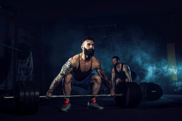 Deux athlètes musclés tatoués barbu s'entraînant au gymnase