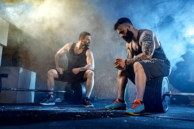 Deux athlètes tatoués barbus musclés se détendent après l'entraînement, soulevant des poids lourds