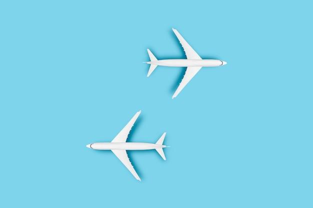 Deux avions sur fond bleu. voyage conceptuel, billets d'avion, vol, itinéraire de palette, transfert.