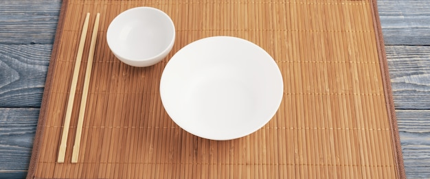 Deux baguettes en bois et deux bol blanc sur un tapis en bambou