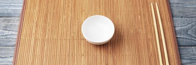 Deux baguettes en bois et une tasse blanche sur un tapis en bambou