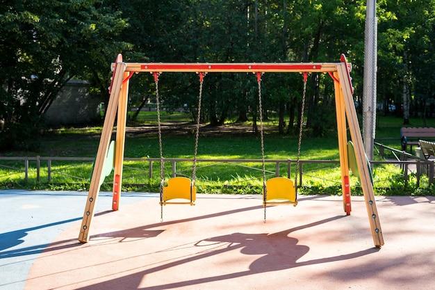 Deux balançoires pour enfants dans une aire de jeux vide en raison de la sécurité des coronavirus pour les enfants bébé balançoires en métal