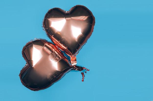 Deux ballons en forme de coeur sur fond bleu