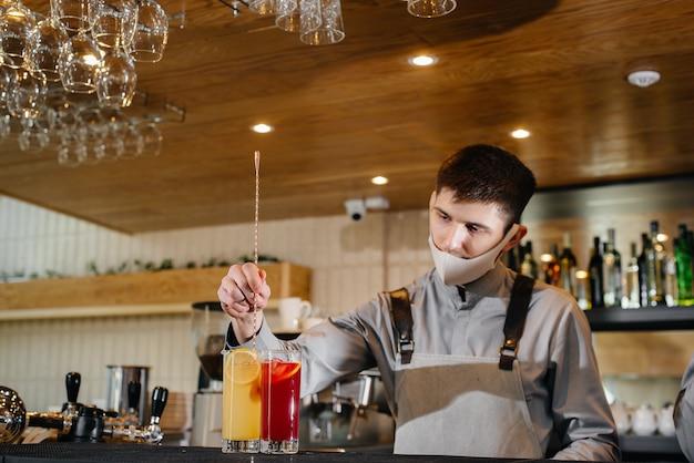 Deux barmans élégants en masques et uniformes pendant la pandémie, préparant des cocktails