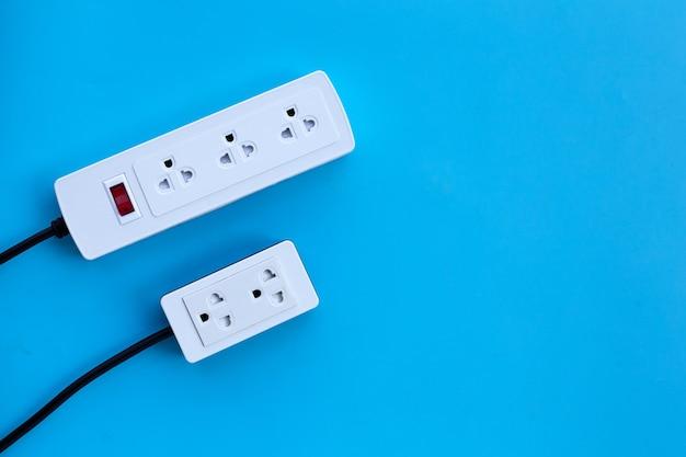 Deux barrettes d'alimentation électrique sur mur bleu. vue de dessus