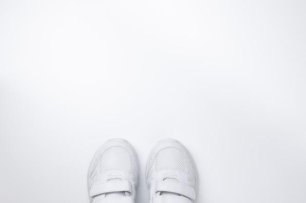 Deux baskets blanches à plat situées partiellement en bas au centre avec un espace libre pour le texte i...
