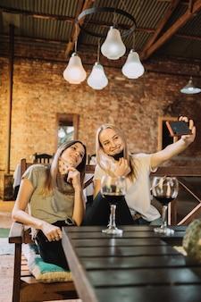 Deux beaux amis caucasiens portant des masques de protection et prenant un selfie - photo d'un couple de belles femmes