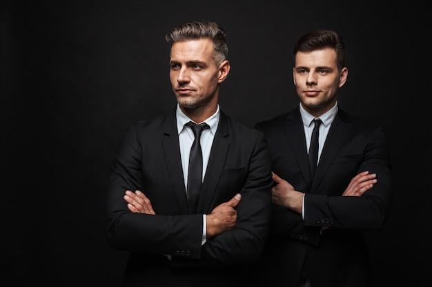 Deux beaux hommes d'affaires confiants portant un costume debout isolés sur un mur noir, les bras croisés