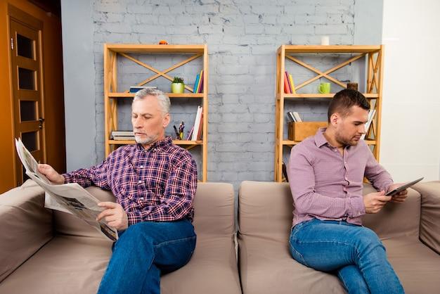 Deux beaux hommes assis sur un canapé et lisant des nouvelles