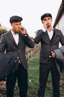 Deux beaux hommes en costume fumant au ranch