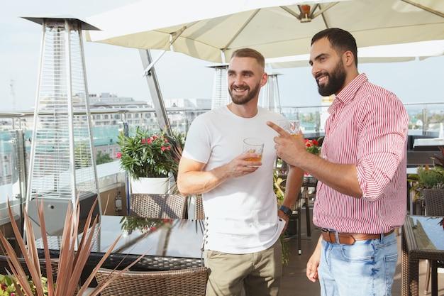 Deux beaux hommes élégants parlant autour d'un verre au restaurant sur le toit moderne, espace copie