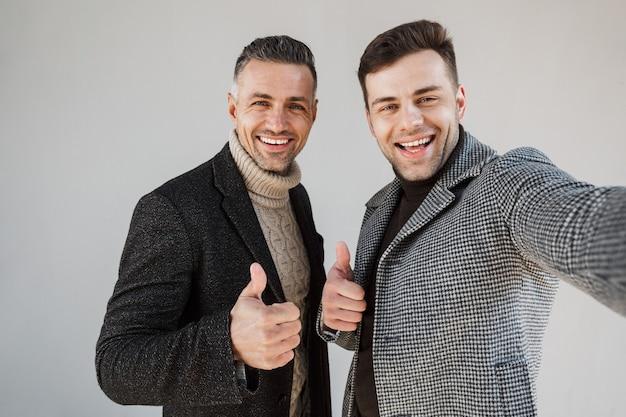 Deux beaux hommes portant des manteaux sur un mur gris, prenant un selfie