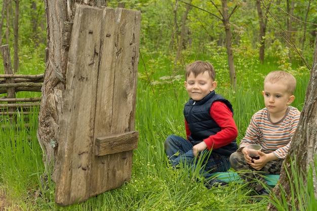 Deux beaux jeunes garçons jouant dans les bois