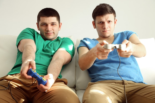 Deux beaux jeunes hommes jouant à des jeux vidéo dans la chambre