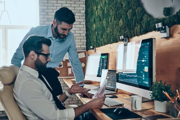 Deux beaux jeunes hommes modernes en tenue de soirée travaillant à l'aide d'ordinateurs assis au bureau