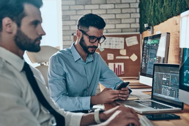 Deux beaux jeunes hommes modernes en tenues de soirée travaillant à l'aide d'ordinateurs assis au bureau
