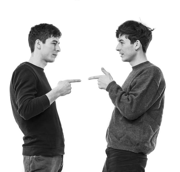 Deux beaux jeunes hommes posant sur un mur blanc