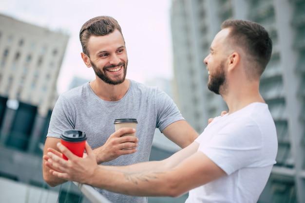 Deux beaux jeunes meilleurs amis barbus dans des vêtements décontractés sont debout en plein air avec des tasses de café en riant et ont une conversation.
