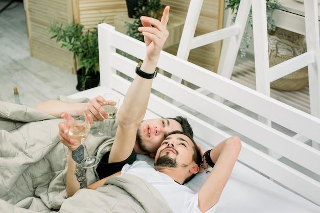 Deux beaux mecs boivent du vin blanc. allongé dans son lit à la maison. jeune, gay, couple, mensonge, couverture, lit, lumière, salle