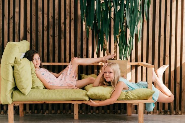 Deux beaux modèles en robes colorées, allongé sur le lit à l'intérieur et posant avec l'expression du visage