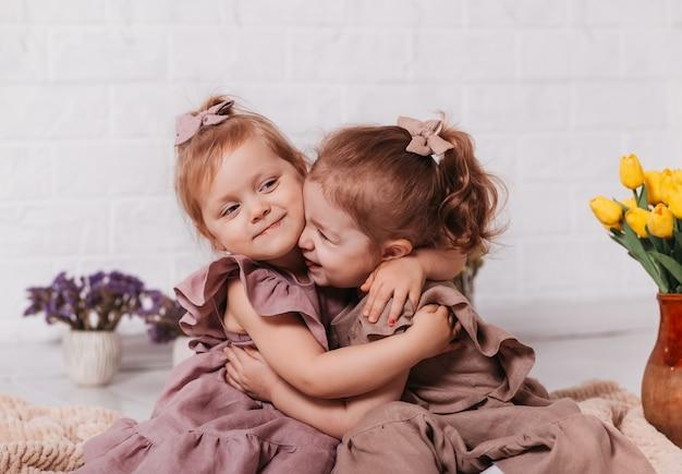Deux bébés filles câlins et sourire dans une chambre avec des fleurs