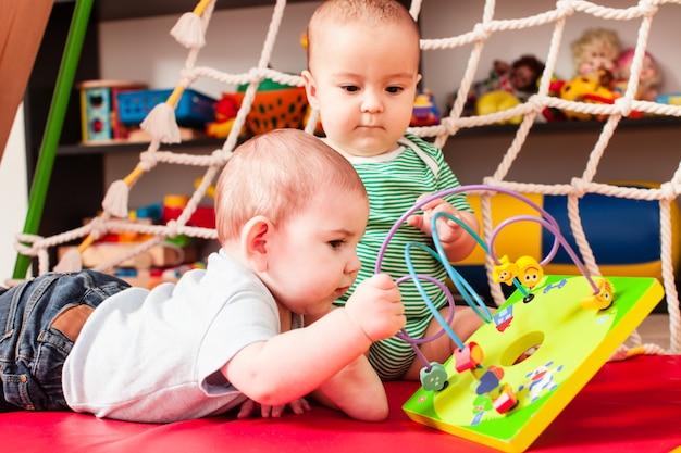 Deux bébés garçons intelligents jouant avec des jouets dans la salle de jeux