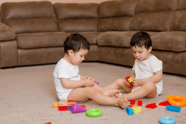 Deux bébés garçons jumeaux sont assis sur le sol de la maison et jouent à des jeux éducatifs. enfant jouant avec des jouets colorés.