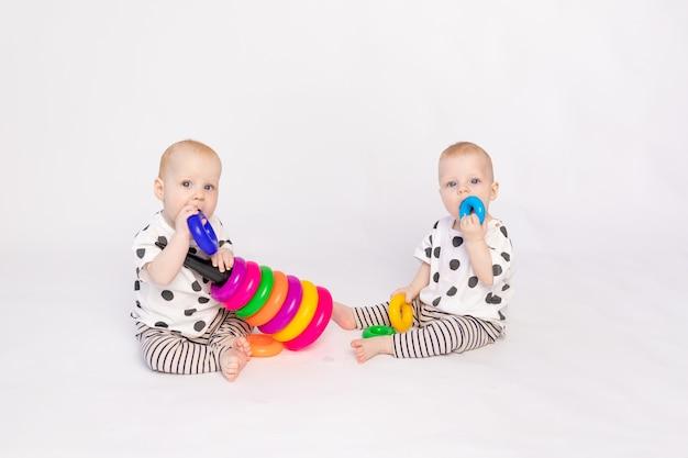 Deux bébés jumeaux jouent sur un fond blanc isolé, développement précoce des enfants jusqu'à un an, un enfant prend un jouet d'un autre, une place pour le texte