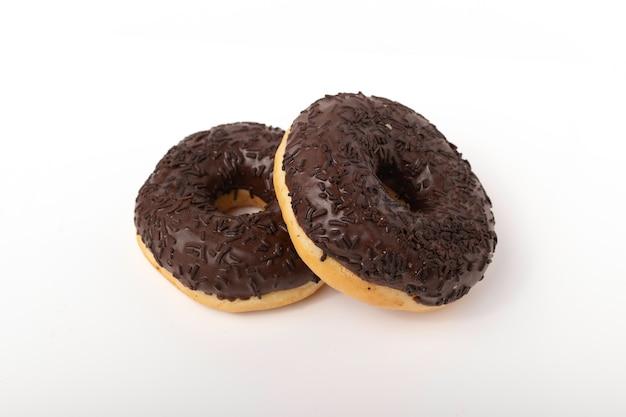 Deux beignets au chocolat avec des pépites sur un blanc