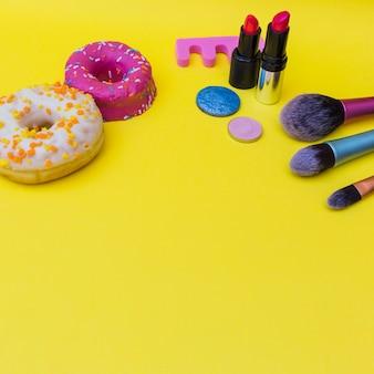 Deux beignets au rouge à lèvres; ombre à paupières et trois pinceau de maquillage sur fond jaune