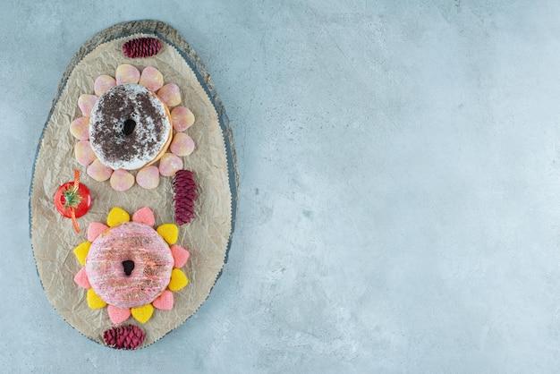 Deux beignets entourés de confitures sur une planche de bois sur marbre.