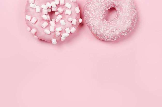 Deux beignets avec glaçage sur rose pastel