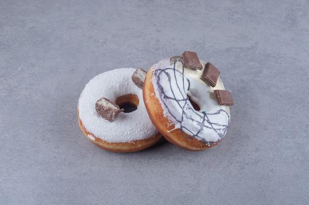 Deux beignets ornés de chocolat sur une surface en marbre