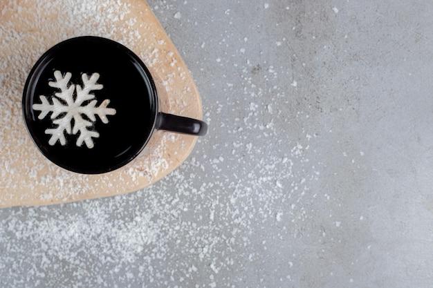 Deux beignets et une tasse de thé avec une décoration de flocon de neige, sur une planche avec de la poudre de coco saupoudrée sur une table en marbre.