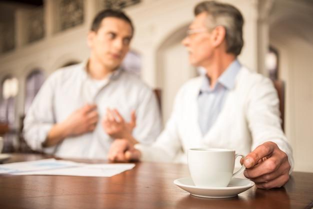 Deux bel homme d'affaires assis et buvant du café.