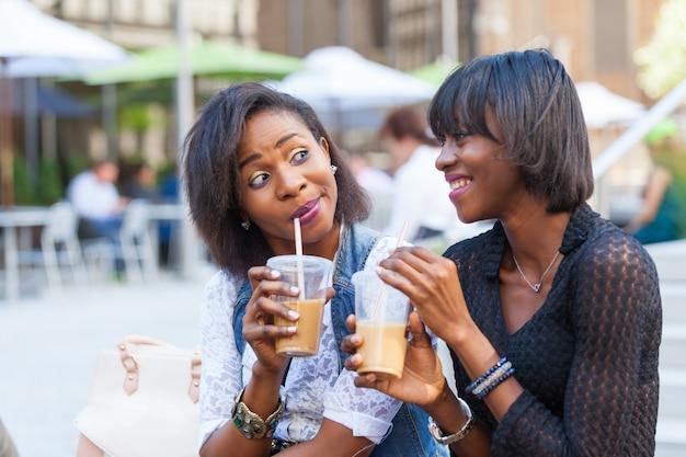 Deux belle femme noire profitant de boissons rafraîchissantes à new york