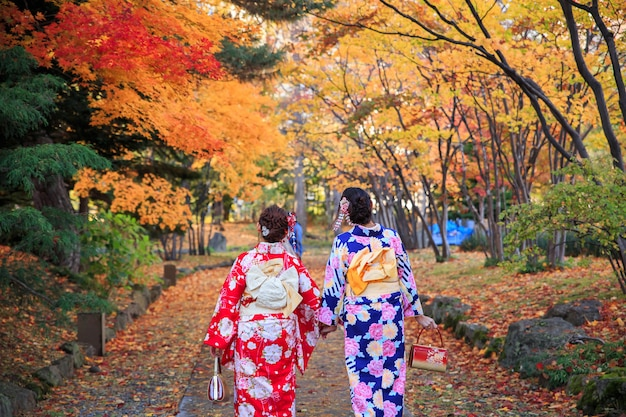 Deux belle fille portant un kimono traditionnel japonais en automne.