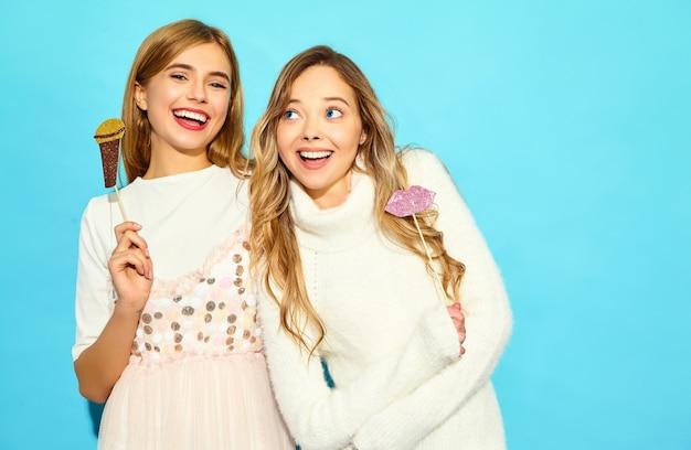 Deux belle jeune femme chantant avec des accessoires faux microphone. femmes à la mode dans des vêtements d'été décontractés. modèles drôles isolés sur mur bleu
