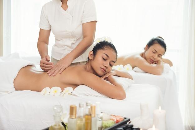 Deux belle jeune femme se spa salon de massage et une fleur blanche sur sa tête.
