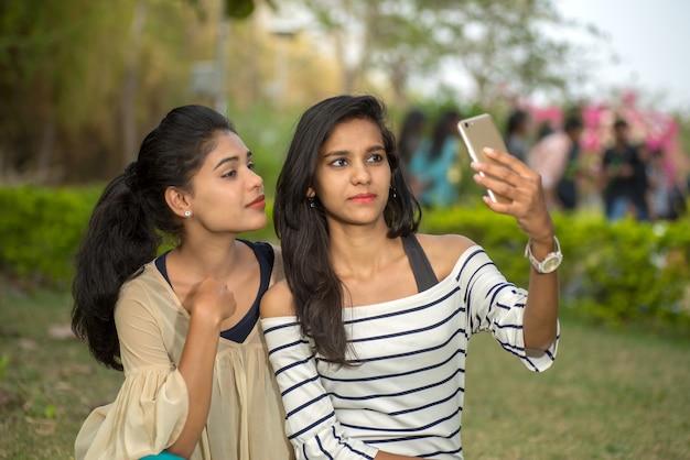 Deux belles amies prenant selfie avec smartphone à l'extérieur.